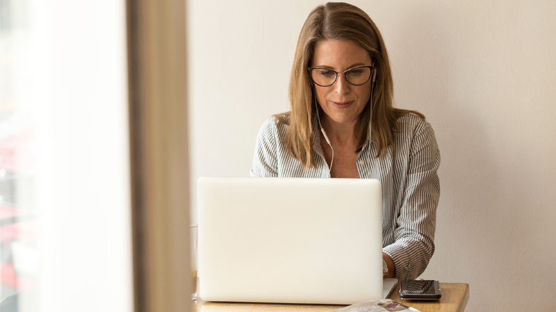 Woman sitting at laptop with white ear buds