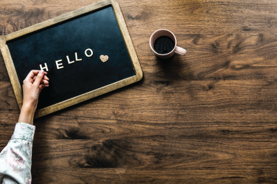 Hello board on wood table with coffee