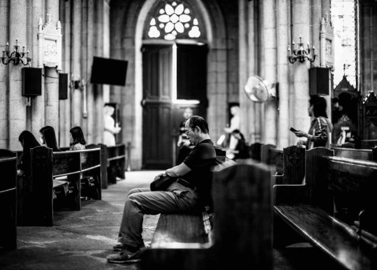 Black and white photo of an asian man sitting in a church pew