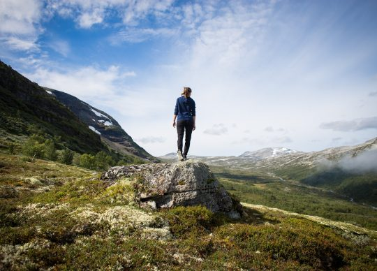 Female hiker standing on a rock looking at a mountain
