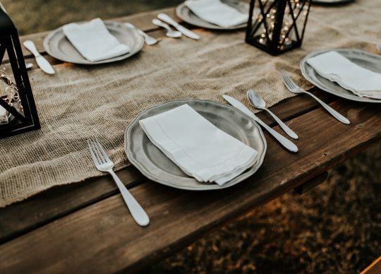 Wooden dinner table set with silver plates